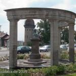 Gesamtansicht des Duncker-Denkmals vor dem Bahnhof Rathenow mit dem Wasserturm im Hintergrund